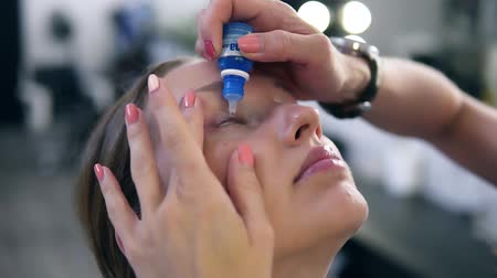 inflammation : Woman with eye drops. Closeup of beautiful girl, make up master applying eyedrops in her eyes. Young female model with natural makeup Stock Footage