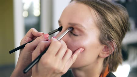 rubs : The professional make-up artist does make-up for the young cute model. Artist putting an eyes shadows using two brushes and does it together. Close up Stock Footage