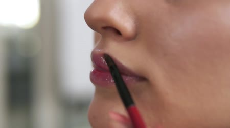 contornos : Closeup view of a professional makeup artist applying lipstick on models lips working in beauty fashion industry. Close up view of an artists hand using special brush