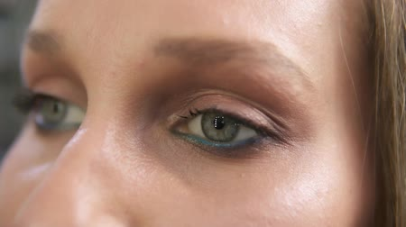 umutlu : Close-up shot of a woman opening her green eyes with light day make-up and focusing them. Attractive beautiful young woman opens her beautiful green eyes