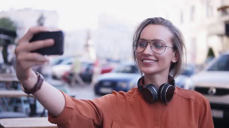 tomar : Cheerful attractive female dressed in orange shirt and sunglasses making selfie on smartphone camera, posing, standing on street. Headphones on her neck Stock Footage