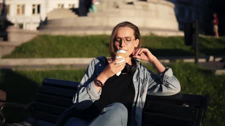 baunilha : Young female in casual clothes enjoying her leisure, sitting on a street bench and licking big vanilla ice-cream. Delisious dessert. Sunny day Stock Footage