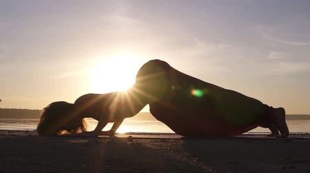 cobra : A silhouette footage of a woman who is doing Urdhva Mukha Shvansana on the beach. Backbend. Sun shines on the background