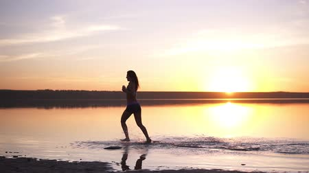 沿岸の : Slender woman with long hair running outdoors. Jogging by the water. Seaside. Sun shines on the background