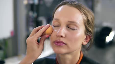 rubs : Professional make up master putting foundation cream on a face. Make up process. Close up of a models face. Make up studio Stock Footage