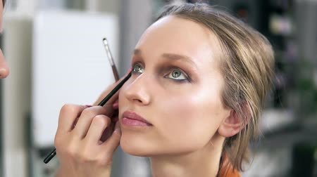 rubs : Make up studio. Professional make up artist doing make up for a beautiful caucasian model. Applying some eyeshadows using a brush. Eyes make up