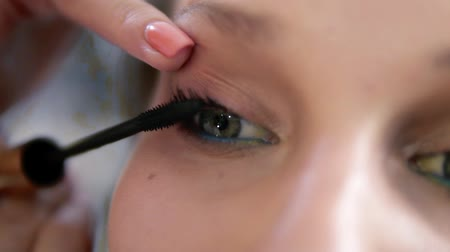 стегать : Extremely close of a young womans eye. Make up artist carefully applying a black mascara. Caucasian model with green eyes