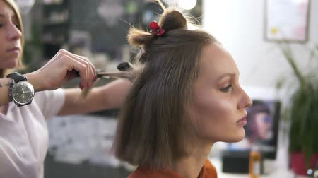 şifoniyer : Side view footage of a beautiful young woman with a casual make up in beauty salon. Professional hairdresser styling her hair with a hair iron. Blonde, short hair model