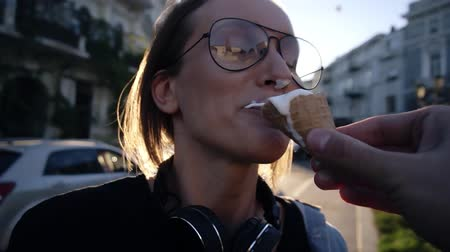 piada : Male hand with a waffle cone ice-cream feeding his girlfriend, Make a joke, poked ice cream in the nose, laughing. Outdoors, city street Stock Footage