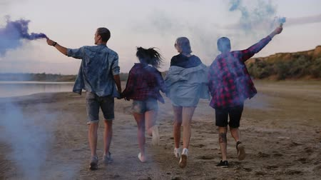 granada : Four friends in casual clothes having fun together. Running and holding hands together. Boys hold in their hands blue smoke boms. Backside view