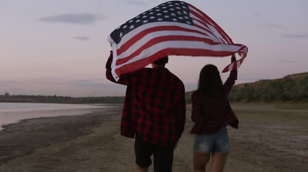 pokrývka hlavy : Young couple both in red plaid shirts are running on the seashore with american flag raised above their heads. Backside view