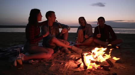 mályvacukor : Two young couples are sitting on the beach near the bonfire. Roasting meat on wooden sticks, eating. Happy time together, picnic. Evening dusk
