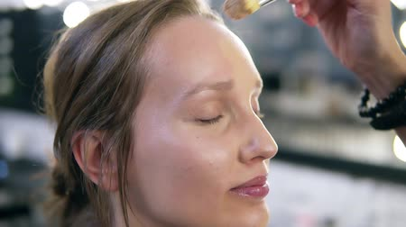 rubs : Close up of face of young woman getting base on her face with a brush. She is smiling. Make up studio