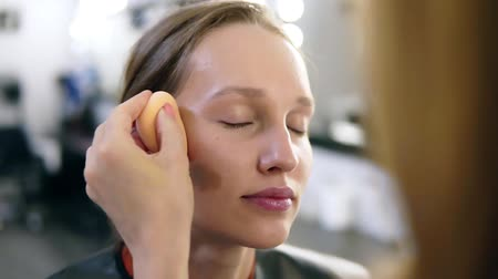 rubs : The make-up artist puts contours on cheekbones of the girl. Professional makeup. Young, blonde model Stock Footage
