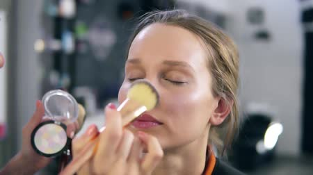 corar : Make-up artist doing make-up accents using shiny shadows. Putting on the face, nose using fingers and a brush. Make up studio. Close up