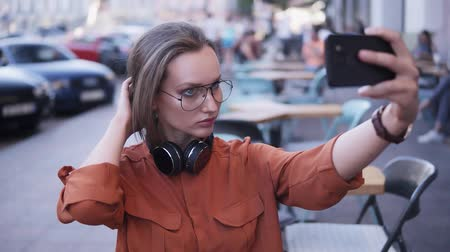 tomar : A stylish girl in the middle of the street takes a photo on her cell phone, fixing her hair, looks for an angle. Headphones on her neck. Cars and people on the blurred background