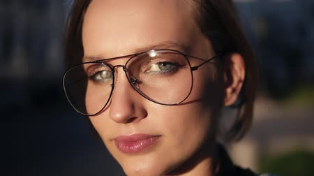ярмарка : Fair hair woman in transparent, modern glasses walking on the street on a sunny day. Looking at the camera. Thoughtful look. Close up Стоковые видеозаписи