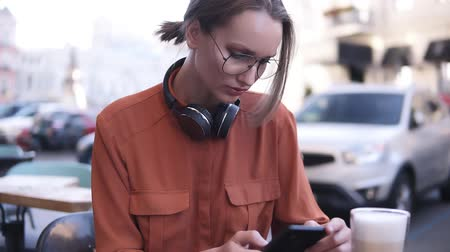 ileri : An attractive blonde girl with hair in a bundle and glasses is sitting in a cafe on the street, next to her on the wooden table a glass of coffee drink. The woman is concentrated in the phone, typing