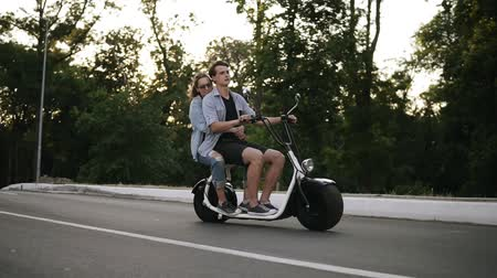 выражающий : Side view of a couple riding on bicycles and having fun. Beautuful young woman and man driving around the city. Freedom, happy lifestyle
