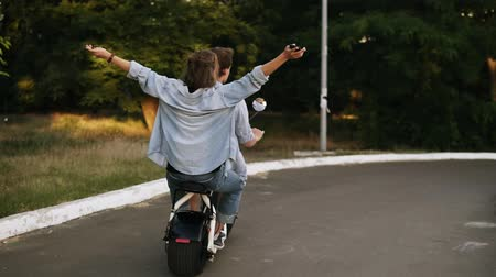 Young, happy cheerful couple riding a minibike in the parkside. Girl is feeling great, outstretched hands. Backside view