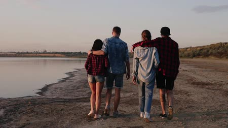 Traking footage of a young caucasian people walking on a beach. Two couples go in an embrace. Backside view