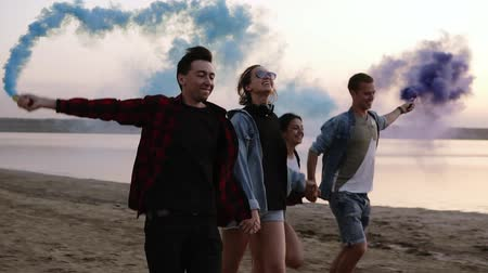 granada : Young four people running with colored smoke grenade in their hands by the sea during sunset. Fun, colorful smoke around them. Smiling, holding with hands together