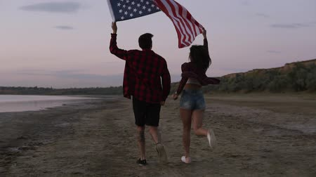 Young woman and man running on the sand with raised american flag, feeling freedom. Evening dusk. Tracking footage Vídeos