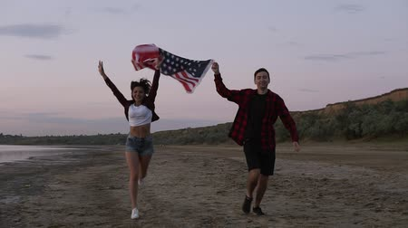 Beautiful young two people running on a seaside in the evening. dusk holding above an american flag. Happy, smiling, emotions Vídeos