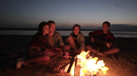mályvacukor : Picnic with friend on the beach near the bonfire.Young people are roasting sausages on wooden sticks. Male from the side is playing the guitar. Night time