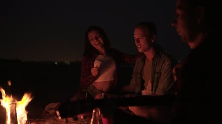 Lovely couple in company emotionally singing a song while their friend is playing the guitar. Bonfire near the sea. Night Vídeos