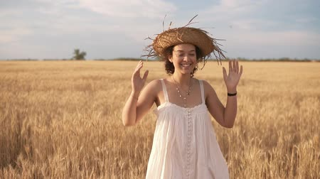 Beautiful brunette curly lady in wheat field at summer. Smiling and posing in straw hat. Front view