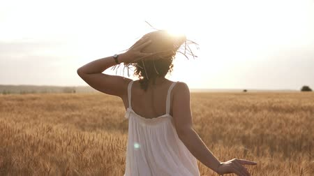 Young woman running in the wheat field while holding her straw hat. Sun shunes in the clear sky. Summer day. Rare view