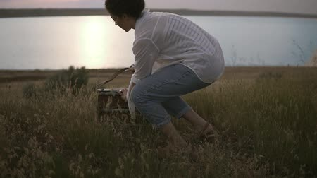 taslakkitabım : Beautiful female art artist preparing her sketchbooks and easel to the work. Lake and clear blue sky in the evening dusk. Nature