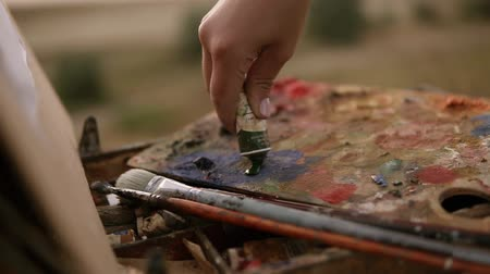 talent : Art, creativity and people concept. Close up of artist extrudes paint from the tube on the palette outdoors Stock Footage