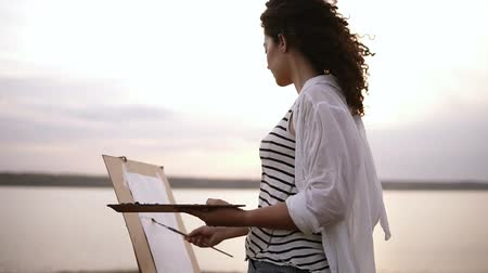 Beautiful curly girl draws a picture on the meadow near the lake using a palette with paints and brush. Easel and paper. Side view