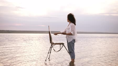 Gorgeous view of a young curly brunette standing in the water with easel and draing her the surrounding landscape. Wearing a blue jeans and white shirt. Full length
