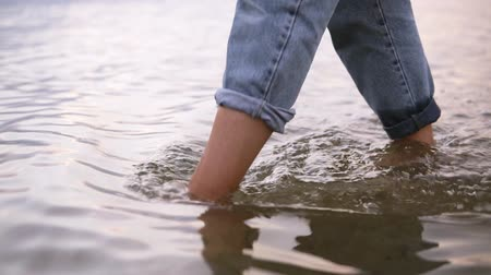 Close up footage of a young womans feet walking by water, lake in blue jeans. Daytime, summer