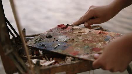 mentiras : Close up shot of the womens hands, who mixes oil paints or scrape off with a palette knife, the colors are on the palette that lies on the easel. Outdoors