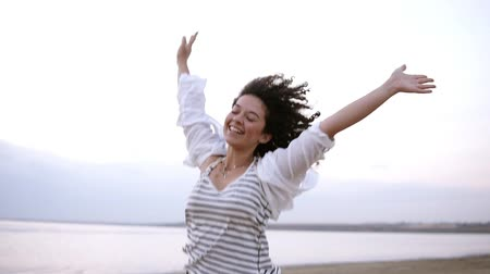 Portrait of a gorgeous curly brunette happily running near the sea or lake with outstretched hands. Wearing white casual clothes. Smiling, happy, freedom