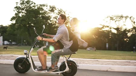 Young man and her girlfriend are riding an electric bile in the crowdy green park. Wearing casual. Happy moments, enjoying life Vídeos