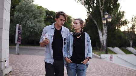 Front view of a couple walking in the park. Wearing similar clothes and shoes. Carefree, loving couple bonding. Evening dusk Vídeos