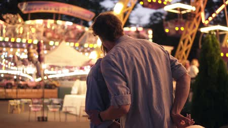 посещающий : Side portrait of an attractive young couple meeting in an amusement park with a colorful, brightful sights. Boy gives a cotton candy to her girlfriend. Holding each other and kissing during a fun night out