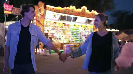 Romantic dating in an amusement park.Young couple walking by funfair at night. Girl is holding a cotton candy and having fun, dancing with his boyfriend. Slow motion Vídeos