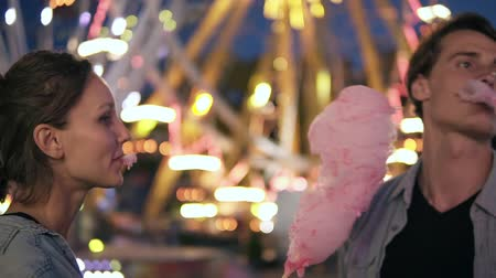 Two hipsters on dating in funfair at night. Having fun together, eating cotton candy together, smiling. Wearing similar clothes
