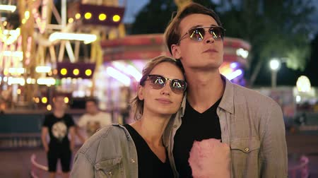 Portrait of stylish hipster young couple in sunglasses are standing and looking thoughtfully for attractions at amusement park at night. Eating pink cotton candy Vídeos