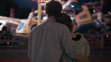 Young couple visiting an amusement park arcade together and hugging while standing next to a carousel ride with lights at night. Standing from the back Vídeos