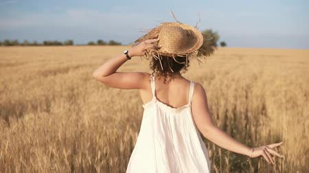 Tracking footage of a beautiful girl in white summer dress and straw hat running freely by wheat field. Backside view