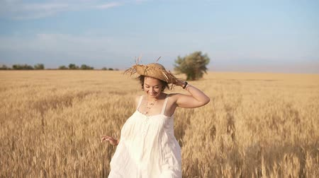 Gorgeous young woman in white dress runnung in the wheat field. Smiling, happy female running and holds her straw hat on her head. Front view