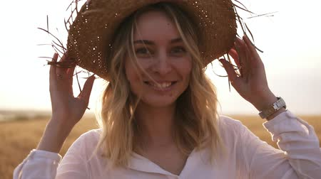 Attractive, funny, smiling blonde woman in white shirt and straw hat posing while walking by wheat field on sunny summer day Vídeos