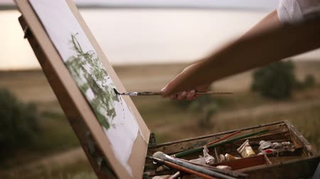 Close up of artist working on her future picture standing outdoors on a green meadow near the lake. Puts colours on canvas using a paintbrush and palette